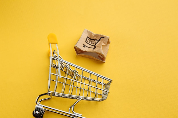 Поврежденная бумажная коробка и тележка для покупок на желтом фоне. концепция доставки. отгрузка авария.