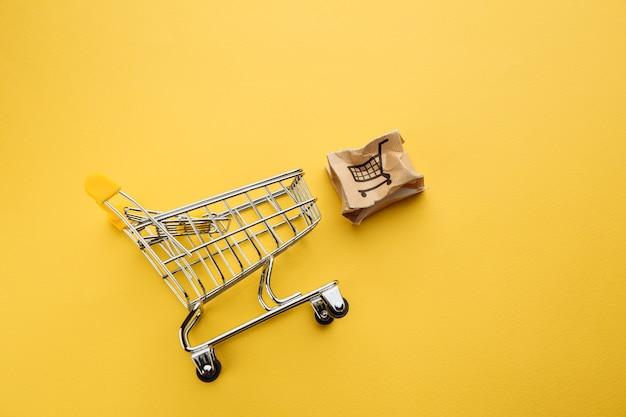 Поврежденная бумажная коробка и тележка для покупок на желтом столе.