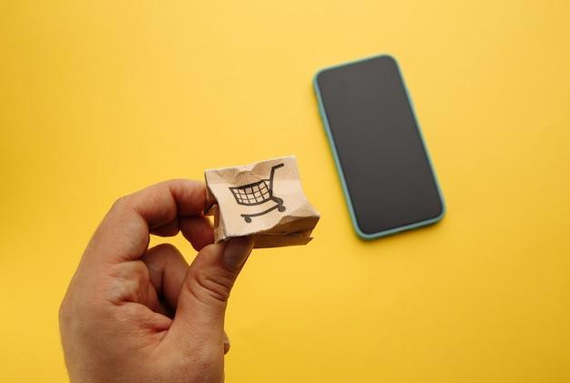 スマートフォンの近くの男性の手で破損した紙箱。オンラインショッピング、サービス、配送のコンセプト