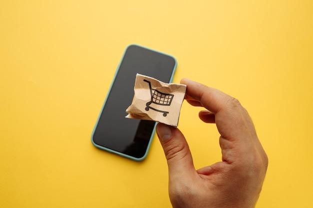 男性の手で破損した紙箱。オンラインショッピング、サービス、配送のコンセプト。