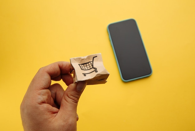 Damaged paper box in male's hand near smartphone. online shopping, service and delivery concept