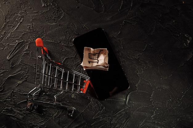 Поврежденная бумажная коробка на экране смартфона и тележки. интернет-магазин, концепция обслуживания и доставки
