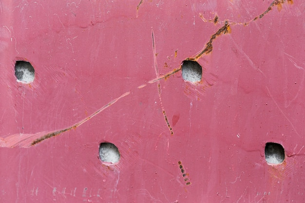 Damaged pink wall texture with holes