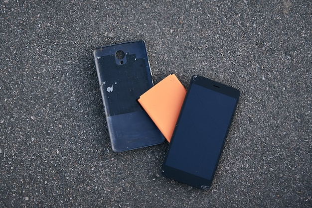Damaged smartphone with broken touch screen on the asphalt