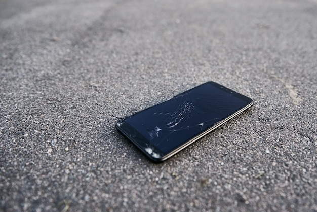 Поврежденный смартфон со сломанным сенсорным экраном на асфальте