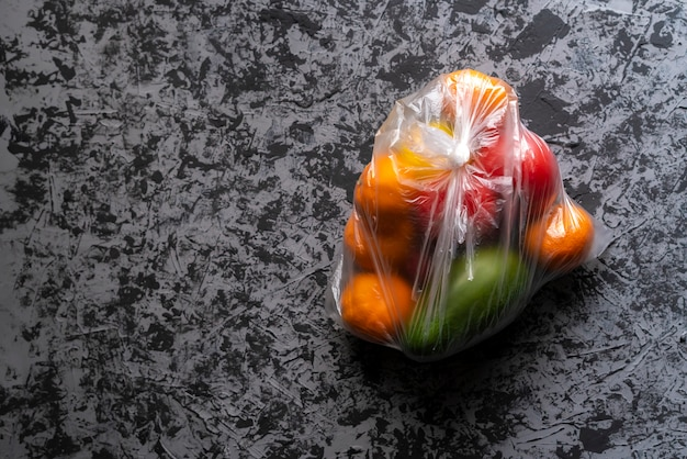 Damaged spoiled fruits in a bag in a dark room, plastic container harm