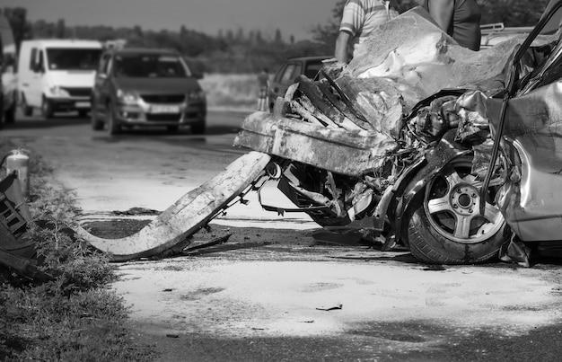 交通事故後の損傷した車両のクローズアップ。黒と白の画像