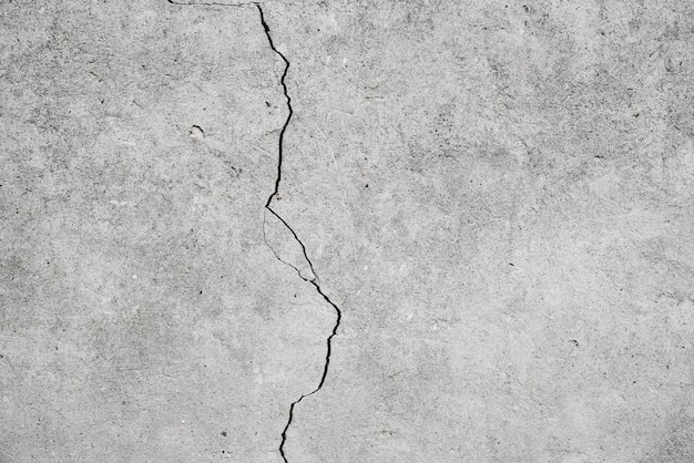 Damaged wall. gray background with a crack