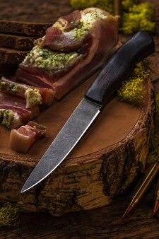 木製の背景にスライスしたベーコンの近くのダマスカスハンティングナイフ