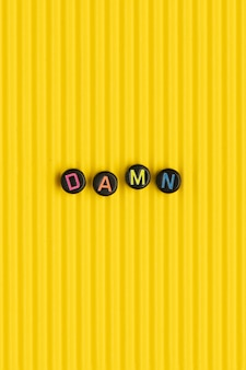 Damn beads text typography on yellow
