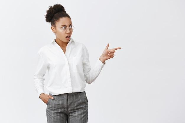 くそー、女の子、あなたが着るもの。メガネとスーツに黒い肌の不快で強烈で混乱している女性同僚の肖像画