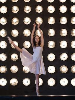 Танцевать. артист балета танцует в темном зале с лампами. юонг женщин балерина упражнения