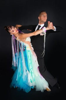 Dance ballroom couple in colorful dress dance pose isolated on black background sensual