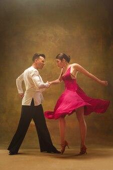 스튜디오 배경에서 춤을 추는 금색 드레스를 입은 댄스 볼룸 커플.