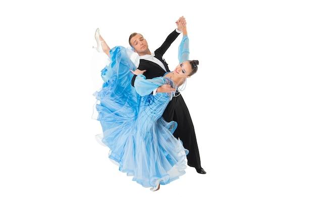 Танец бальных пар в красном платье танцевальной позы изолирован на черном фоне. чувственные профессиональные танцоры танцуют вальс, танго, медленный лис и квикстеп.