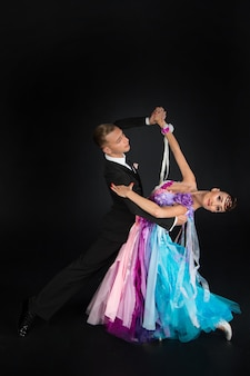 Dance ballroom couple in red and blue colorful dress dance pose isolated on black background. sensual professional dancers dancing walz, tango, slowfox and quickstep.