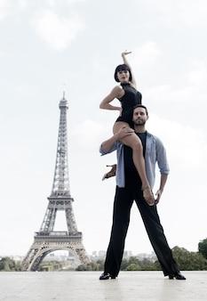 パリ、フランスのエッフェル塔の前でカップルを踊ります。エッフェル塔の近くでダンスポーズをとる美しい社交ダンスのカップル。ロマンチックな旅行のコンセプト。官能的な気持ちと愛