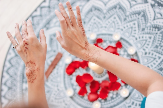 Dance of female hands with mehendi over the altar of candles and rose petals