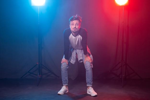 Танцы, хип-хоп и реггетон концепции - молодой человек танцует над огнями.
