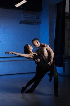 Dance partners practicing in dark studio