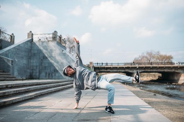 Dance performer, hip hop dancing  on the street. modern dance style. male dancer, cityscape