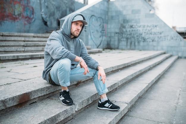 Исполнитель танцев, сидя на ступеньках, городской стиль танцев, уличные танцы. мужчина танцор