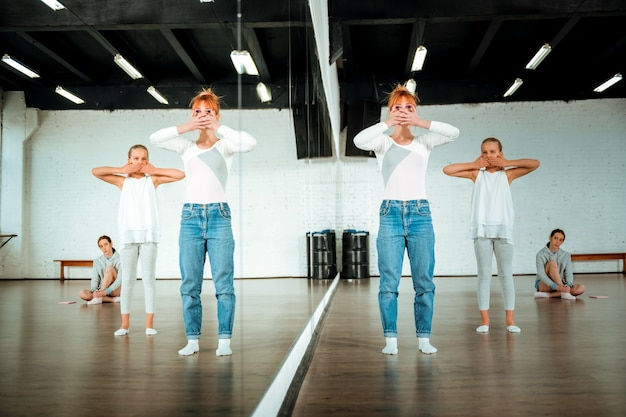 Dance practice. red-haired ballet teacher and her students feeling concentrated while practicing elements of modern dance