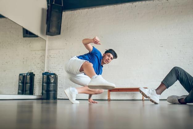 댄스 리허설. 반바지와 운동화에 젊은 집중된 남자가 바닥에 손과 발을 쉬고 댄스 동작을 연습합니다.