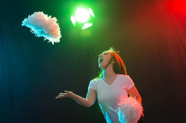 댄스, 스포츠, 그리고 사람들의 개념 - 예쁜 젊은 여성이 폼폼을 들고 어둠 속에서 춤을 추고 웃고 있습니다.
