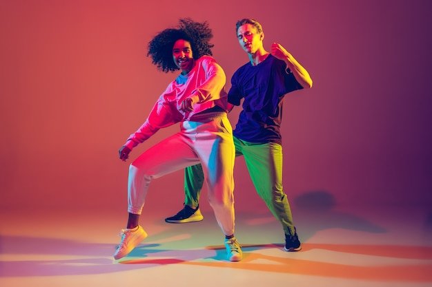Dance time. stylish men and woman dancing hip-hop in bright clothes on green background at dance hall in neon light.