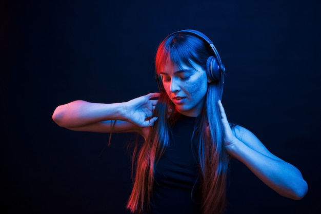 Танцуй в ритме. студия снята в темной студии с неоновым светом. портрет молодой девушки