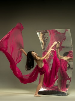 Dance with fire. modern ballet dancer on brown wall with mirror. illusion reflections on surface. magic of flexibility, motion with fabric. concept of creative art dancing, action, inspiring.