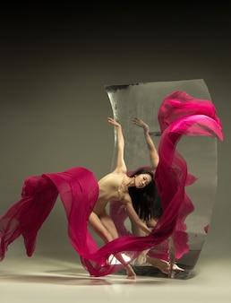 火で踊る。鏡付きの茶色の壁にモダンなバレエダンサー。表面での錯覚の反射。柔軟性の魔法、生地による動き。クリエイティブアートダンス、アクション、インスピレーションのコンセプト。