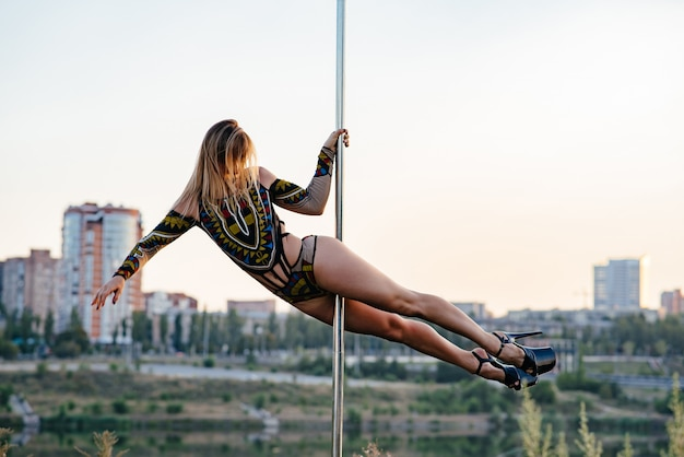Dancer brunette with wavy hair on pole for dancing summer beach