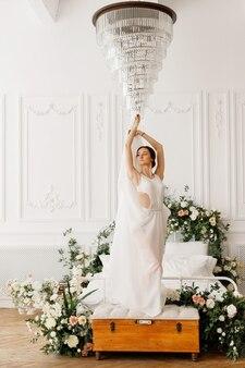 사진 스튜디오에서 침대에서 흰 드레스에 댄서 소녀