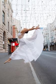 白い服を着たダンサーが街でジャンプします。