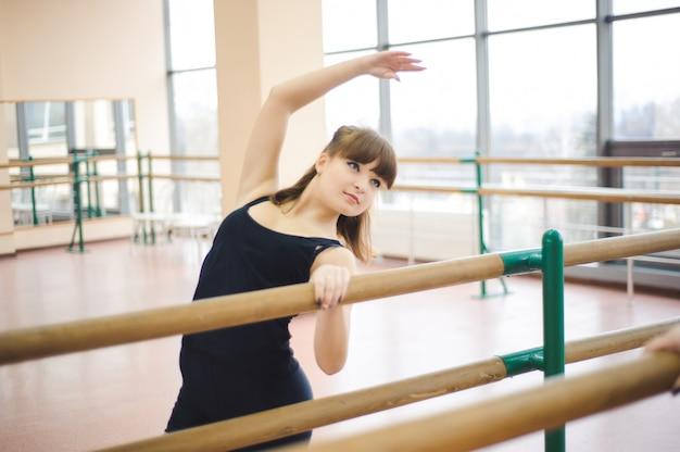 Dancer is doing exercises in the ballet class