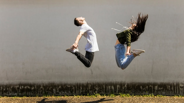 Dancer jumping in air against gray wall