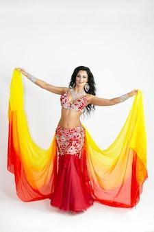 Танцовщица восточных танцев с яркими шарфами из ткани.