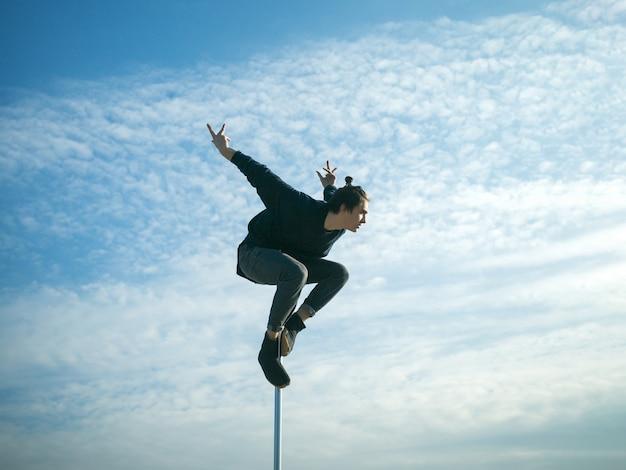 철탑에 곡예 성능을 보여주는 댄서 극 극 댄스 스포츠에 강한 남자 댄서 운동 운동 남자는 철탑에 곡예 요소를 만듭니다