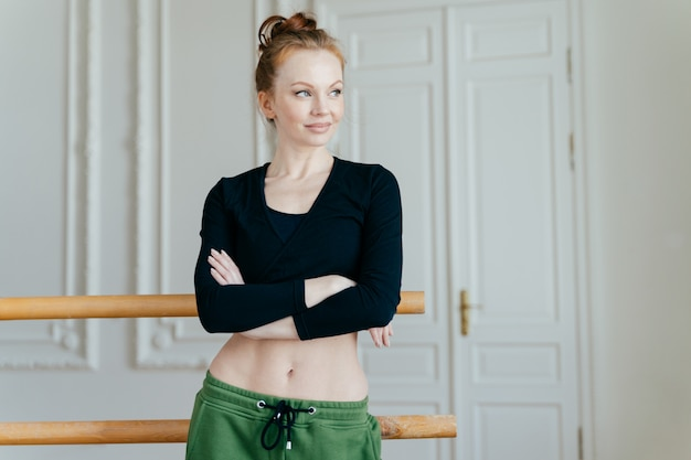 Dancer with athletic body, keeps hands crossed, looks away with thoughtful expression, poses near handrail in dancing studio