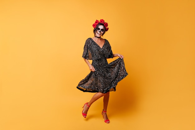 Dancing active mexican model posing on orange background. full-length portrait of girl rejoicing halloween.