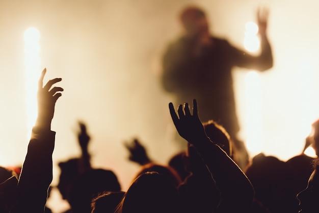 歌手がライトに囲まれて演奏している間にコンサートで踊る