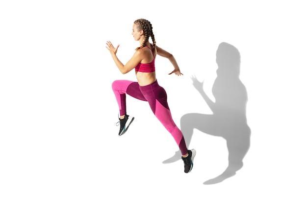 ダンシング。白い壁、影の肖像画で練習している美しい若い女性アスリート。動きとアクションのスポーティーフィットモデル。ボディービル、健康的なライフスタイル、スタイルのコンセプト。