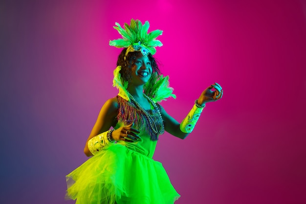 Dancing. beautiful young woman in carnival, stylish masquerade costume with feathers dancing on gradient wall in neon. concept of holidays celebration, festive time, dance, party, having fun.