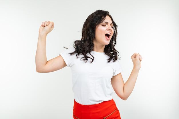 흰색 배경에 고립 된 흰색 티셔츠에 갈색 머리 소녀 춤