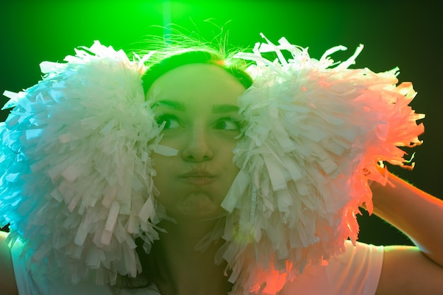 춤, 치어리딩, 그리고 사람들의 개념 - 머리에 폼폼이 달린 화려한 조명 아래 어둠 속에서 재미있는 어린 소녀