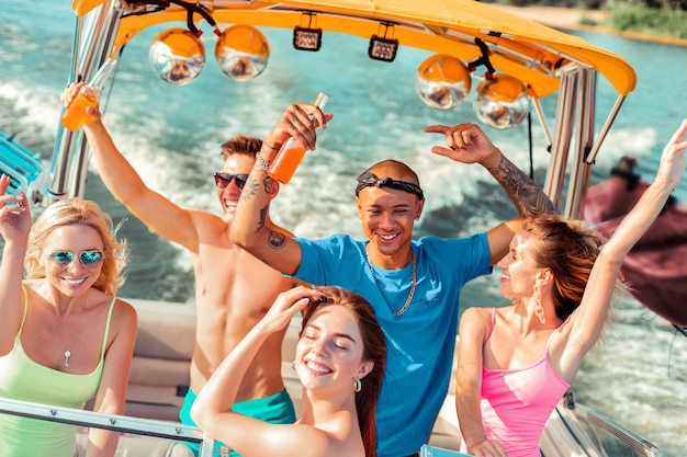 댄스 컴퍼니. 화창한 날씨에 요트 갑판에서 술을 마시고 춤을 추는 잘 생긴 젊은 사람들의 그룹