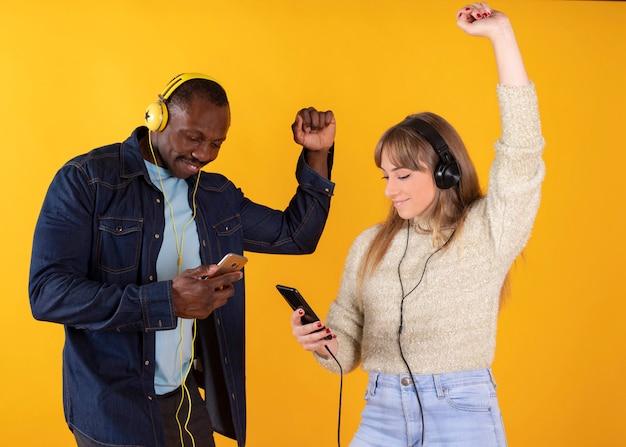 Танцующая пара слушает музыку на своих мобильных телефонах,