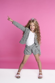 Dancing full length little girl on pink